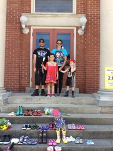 Family visiting memorial on library steps.