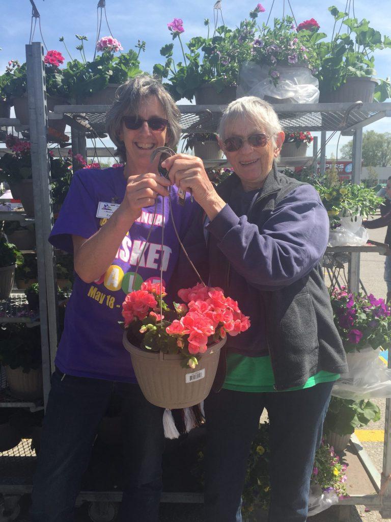 Emma and Susan holding hanging baskets 2019