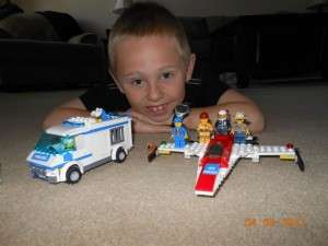 kid smiling with lego creations. kid's zone page.