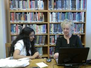 Photograph of teen helping adult computer learner