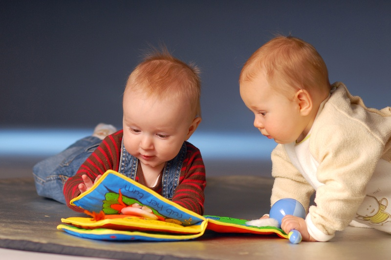 two babies looking a book. image for blooming babies story time post.